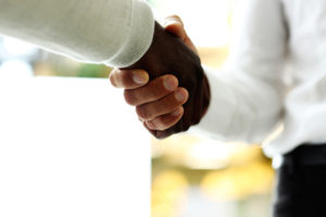 Close up of two people shaking hands.
